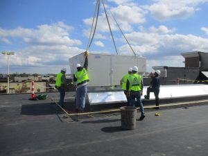 ClearWater team aligning a commercial HVAC rooftop unit in with a crane into its final place.